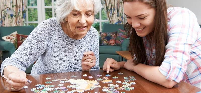 opiekunka z seniorem układa puzzle